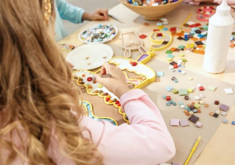 Criança em mesa fazendo artesanato