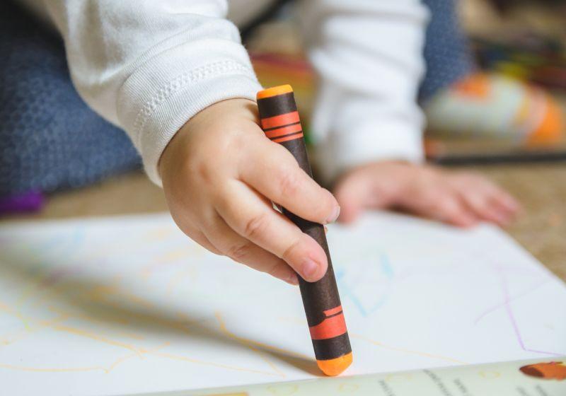 Braço e uma criança pintando com giz de cera de tres cores