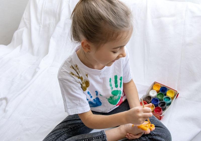 Criança de camiseta branca sentada em um chão branco, segurando lás de core nas mãos