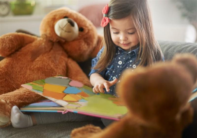 Menina lendo livro ao lado de ursinhos de pelúcia
