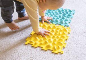 Bebê brincando com tapete de borracha com textura