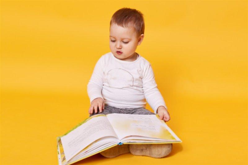 Bebê sentado no chão com livro aberto em seu colo