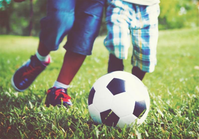 Duas crianças brincando com bola em gramado