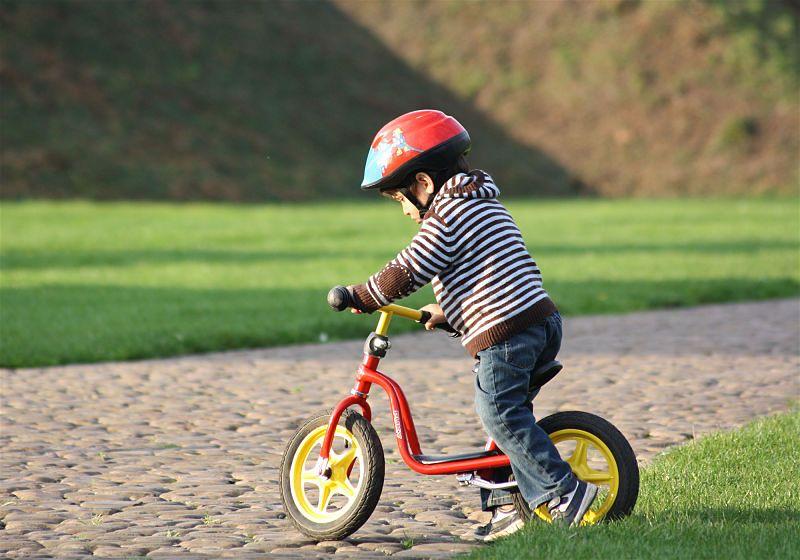 Criança andando de bicicleta em um gramado, com roupas adequadas para a brincadeira