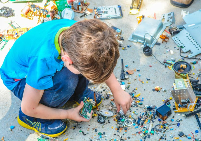 Criança brincando com componentes eletrônicos jogados fora