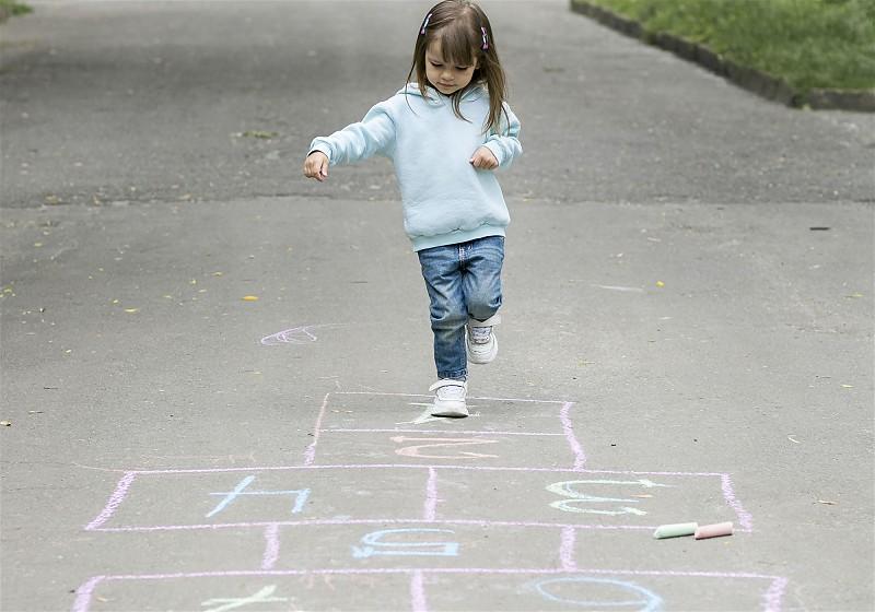 Criança pulando amarelinha