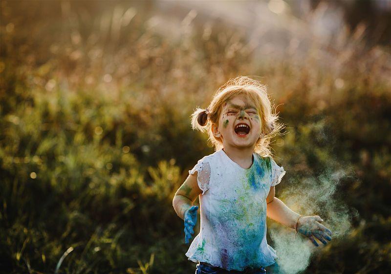 Criança correndo em local arborizado e suja de tinta