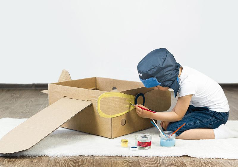 Criança personalizando caixa de papelão