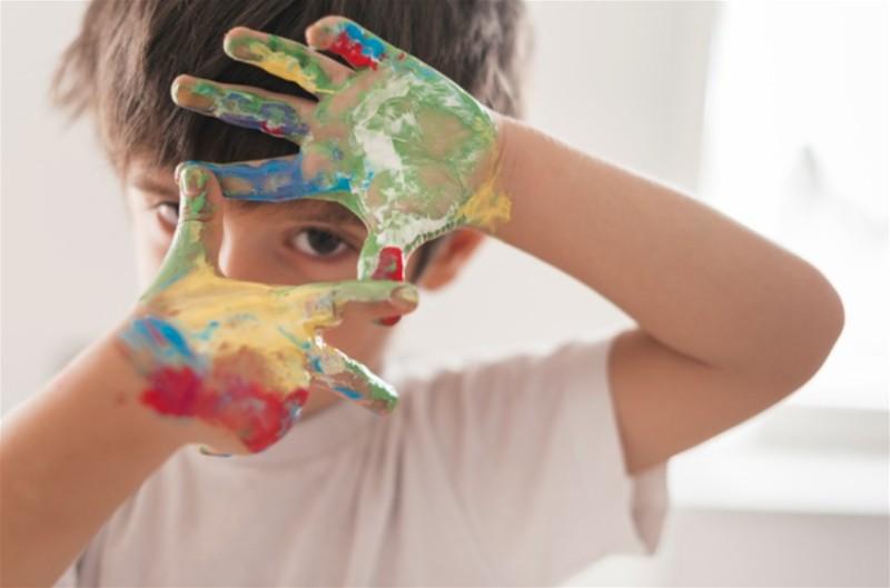 Criança com as mão sujas de tinta