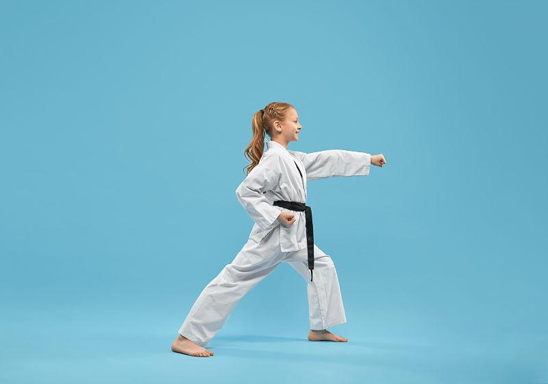 Criança com veste de para a prática de Karatê e praticando o esporte