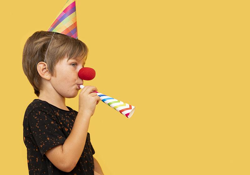 Criança utilizando chapéu de festa, com nariz de palhaço e assoprando um canudo colorido