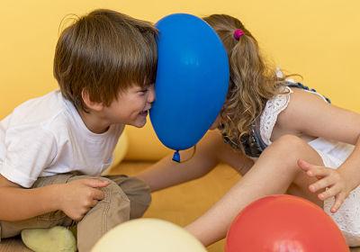 Duas crianças brincando com bexiga, tentado estourá-la com a cabeça