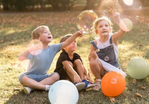 Crianças sentadas em um gramado perto de bexigas e brincando com bolhas de sabão
