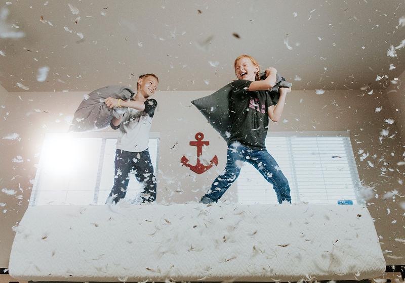 Duas crianças em pé sobre cama brincando com travesseiros e penas voando saindo dos travesseiros