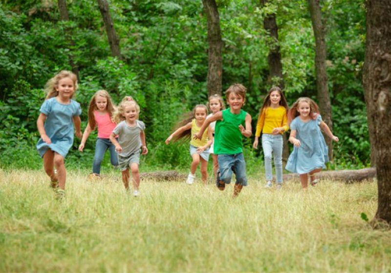 Crianças correndo e local arborizado