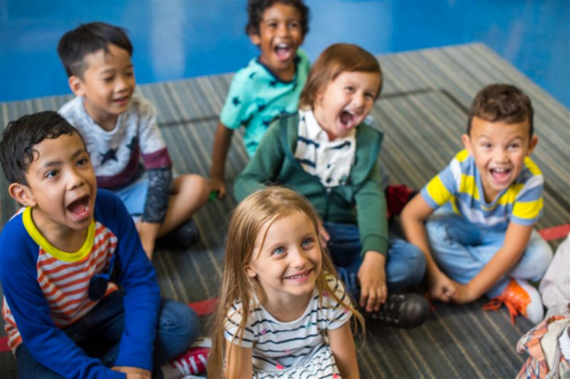 Crianças sorridentes, sentadas e olhando para cima como se estivessem escutando alguém