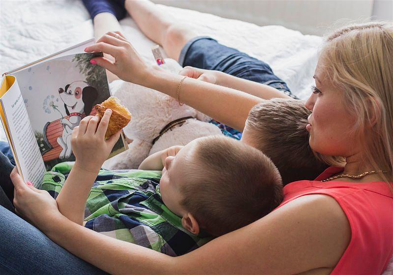 Mãe com livro infantil lendo para duas crianças