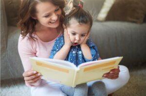 Mãe sentada com filha no colo, lendo livro para ela