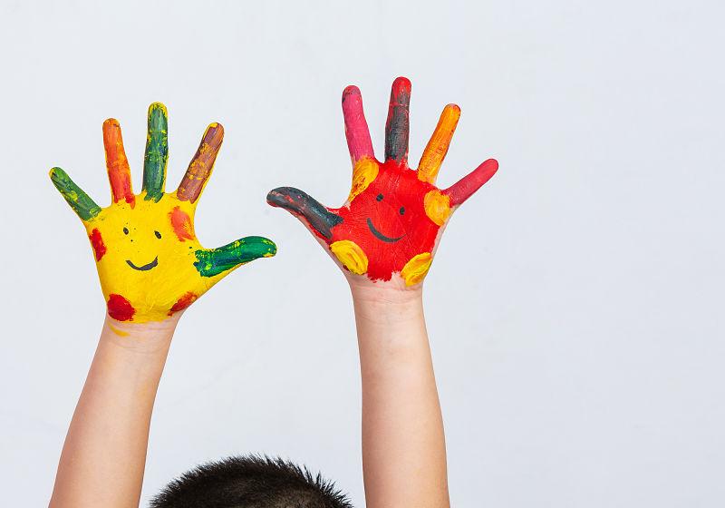 Mãos de criança levantadas e pintadas de tinta, com rostinho simples na palma da mão