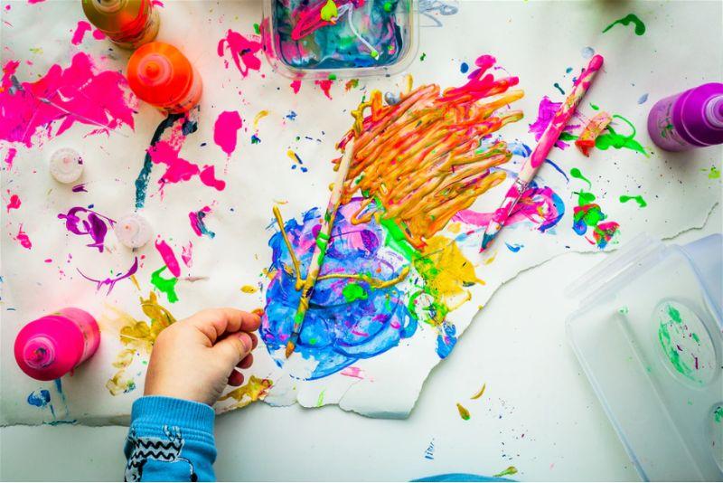 Papel todo pintado com tinta e mão de criança ao lado