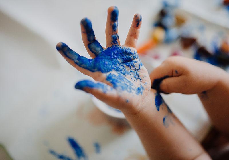 Mão de criança suja de tinta azul