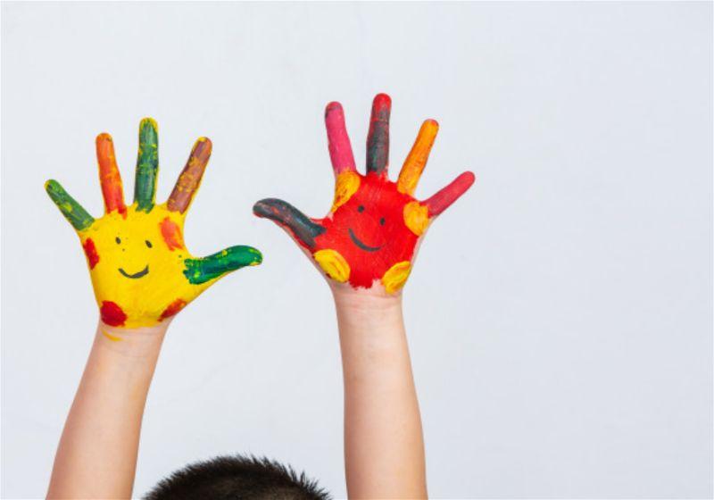 Mão de criança pintada de tinta, com desenho de carinha feliz