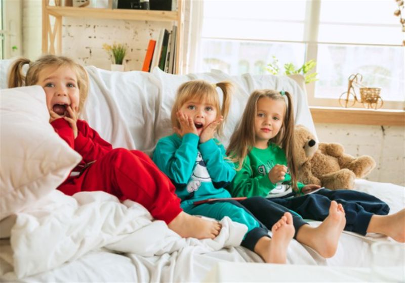 Crianças sentadas em sofá com cara de espanto