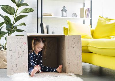 Menina dentro de caixa de papelão fazendo rabiscos no interior da caixa