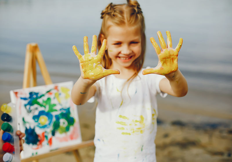 Menina mostrando a palma das mãos sujas de tinta amarela