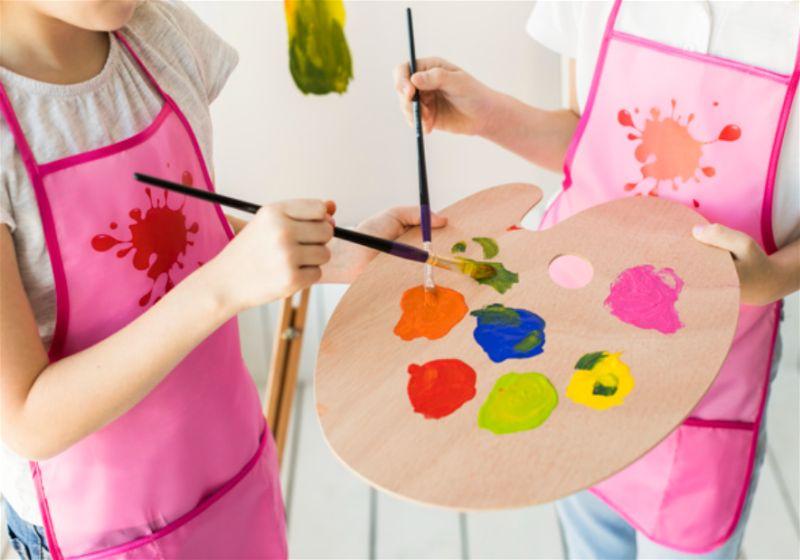 Menina de avental rosa segurando paleta de tinta