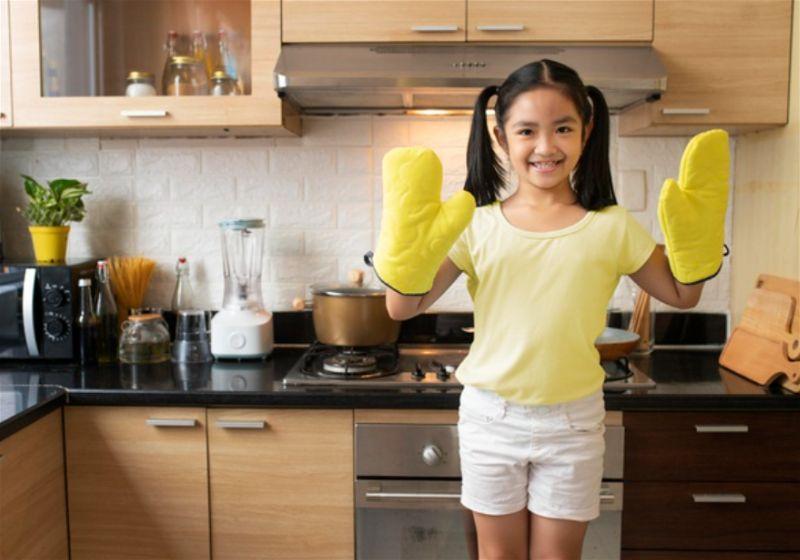 Menina em cozinha utilizando luva