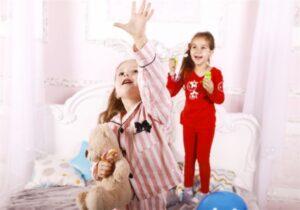 Duas meninas em pé sobre cama, vestidas de pijama