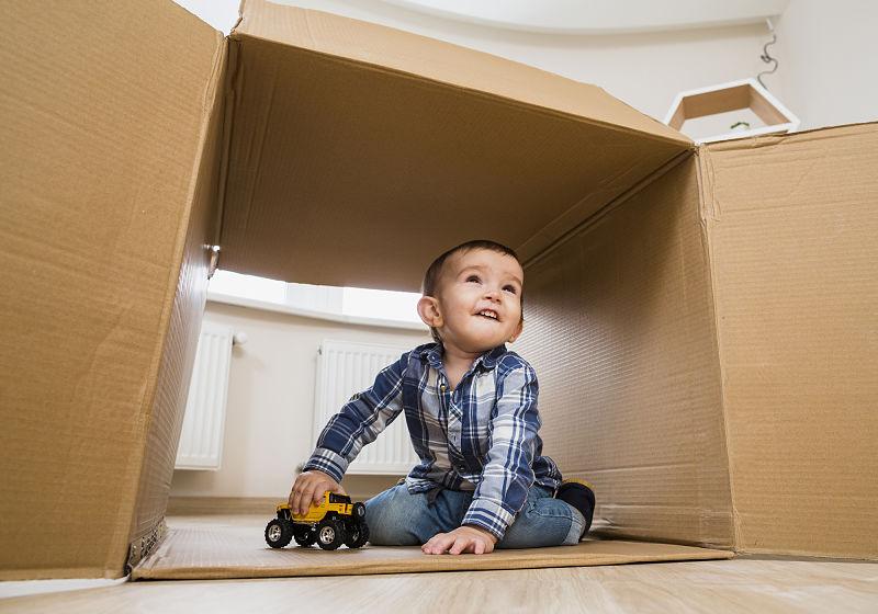 Criança dentro de caixa de papelão brincado com carrinho