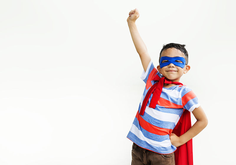 Criança vestida de super heróis com um braço erguido