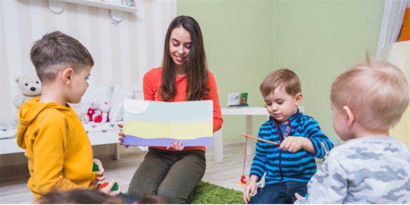Mulher em frente crianças mostrando desenho em papel