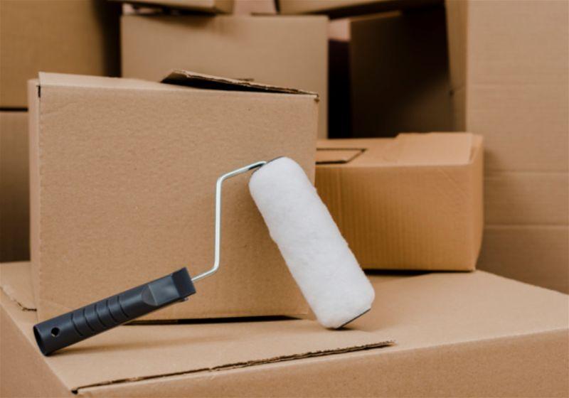 Caixas de papelão e um rolo de pintura sobre elas
